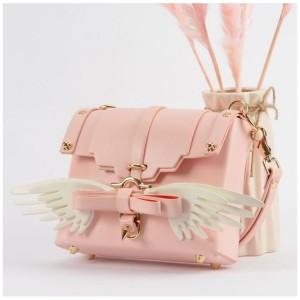 Ružová crossbody kabelka so zlatým kovaním a krídlami